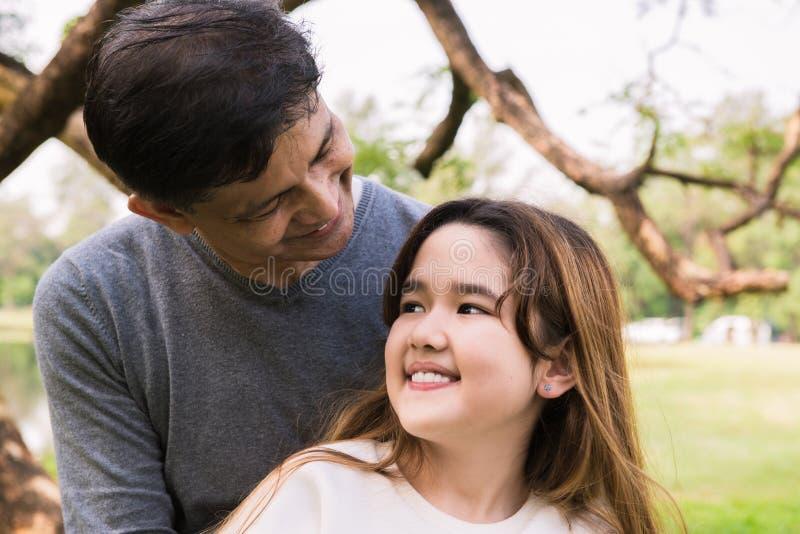 Una pequeña sonrisa de la hija a su padre en el parque fotografía de archivo libre de regalías