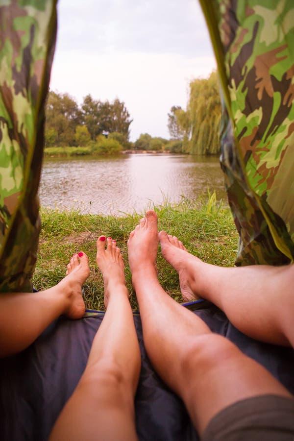Una pequeña tienda de campaña en el lago, el alojamiento de una noche y los pies de un par joven foto de archivo