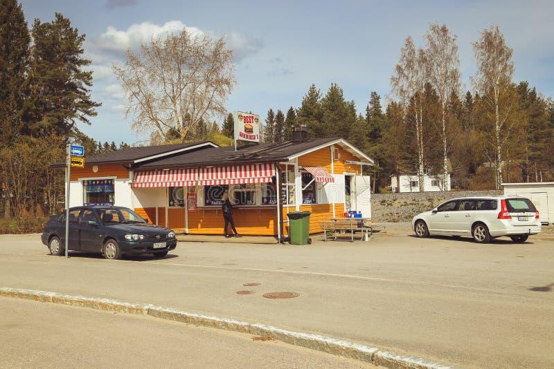 Una peque?a ciudad en Finlandia, un caf? del borde de la carretera, coches en el camino y tiendas D?a de verano de la ciudad finl imagen de archivo