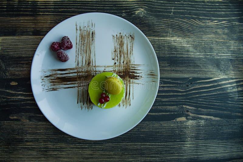 Una peque?a torta del pistacho con una capa verde y adornada con el viburnum, preparaci?n de la confiter?a en un fondo negro Vist fotografía de archivo