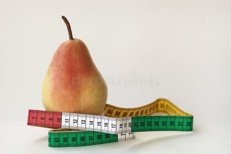 Una pera y cinta métrica maduras en el fondo ligero, concepto de una forma de vida sana, dieta, control del exceso de peso imágenes de archivo libres de regalías