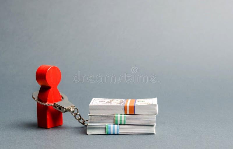 Una persona è ammanettata con una pila di soldi r r Debito enorme da essere fotografie stock libere da diritti