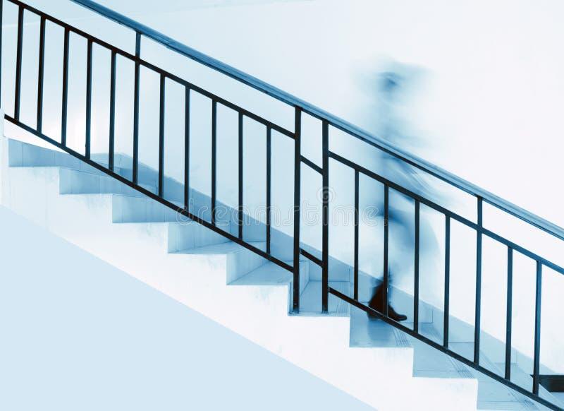 Una persona è sotto le scale fotografia stock libera da diritti