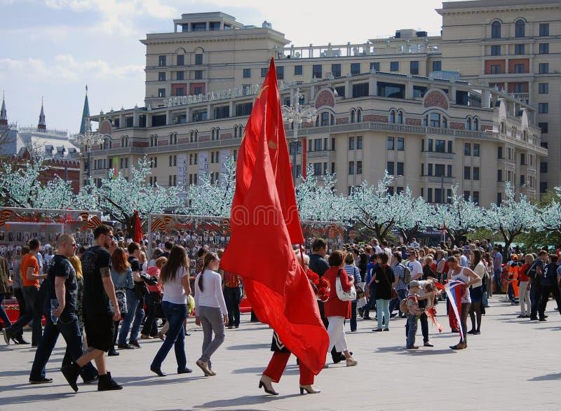 Una persona camina sosteniendo una bandera roja de Unión Soviética foto de archivo libre de regalías