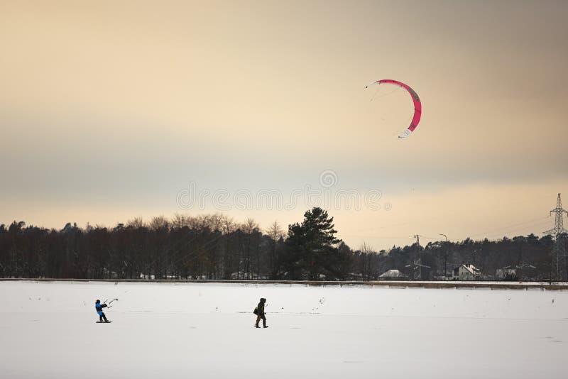 Una persona che kiting con gli aquiloni variopinti nell'inverno su neve fotografie stock libere da diritti