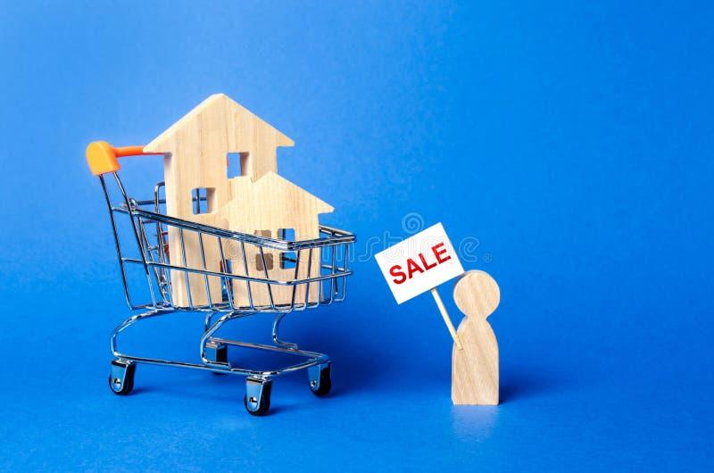Una persona con una muestra en venta se coloca cerca de la casa concepto de vender un hogar, comprando del due?o Compra y venta r imagen de archivo
