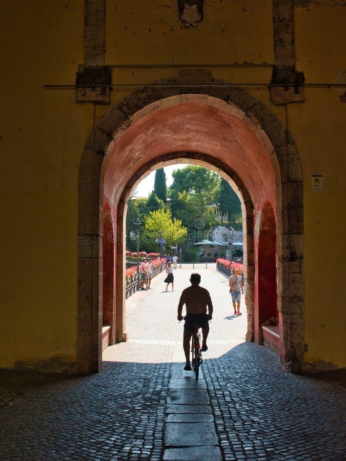 Una persona en una bicicleta sale del pueblo de Peschiera del Garda en el lago Garda, Italia, pasando a través del arco de Porta  fotografía de archivo