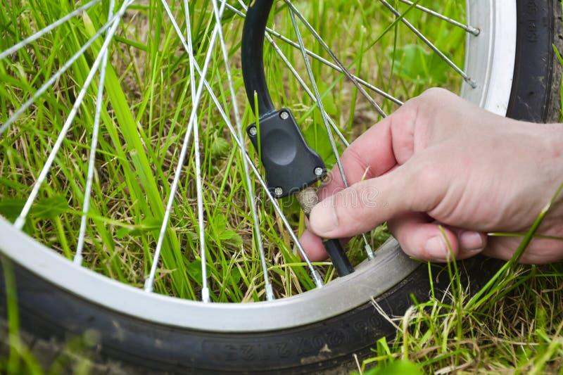 Una persona está inflando una rueda de bicicleta con la ayuda del aire comprimido y de un indicador de presión Rueda y mano vista fotos de archivo libres de regalías