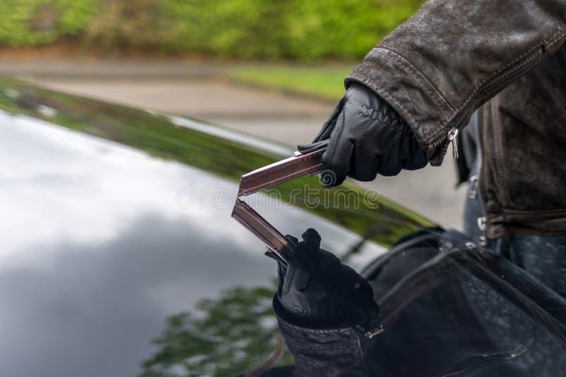 Una persona graffia il cofano di un'automobile con una lama fotografie stock libere da diritti
