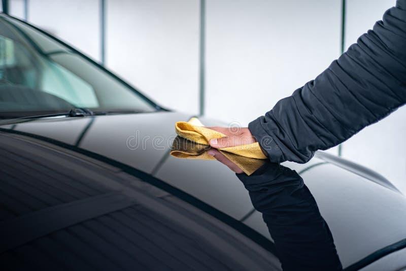 Una persona lucida il cofano sulla sua automobile immagine stock
