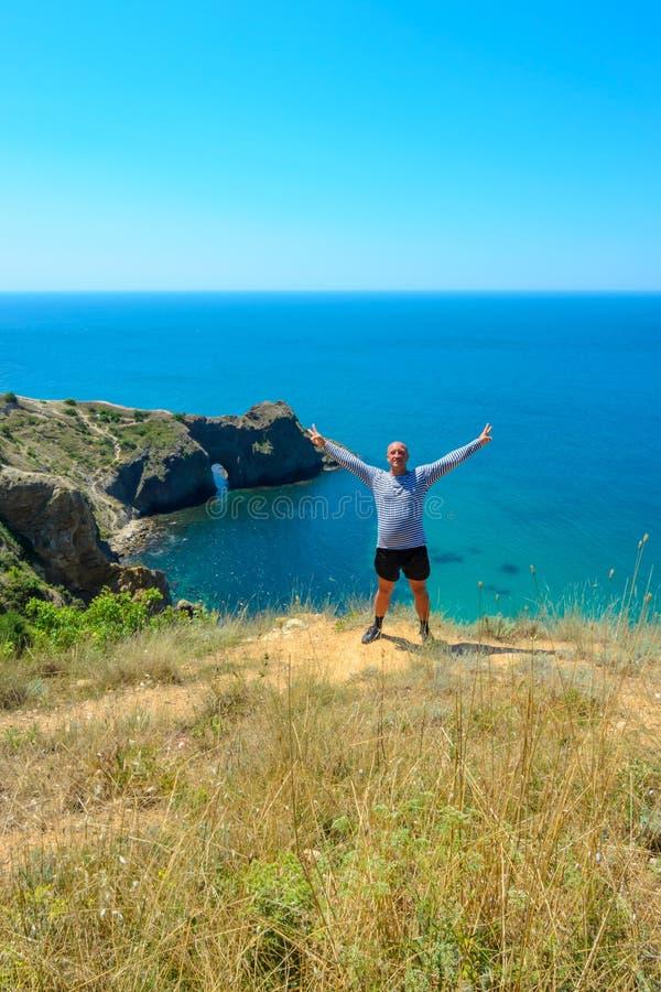 Una persona positiva sta sui precedenti del mare su una scogliera un giorno di estate soleggiato immagine stock
