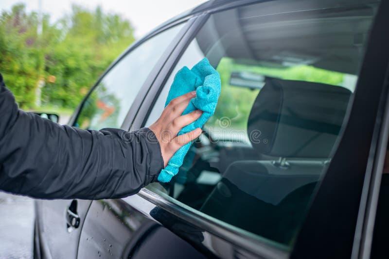 Una persona pule la ventana en un coche fotografía de archivo libre de regalías