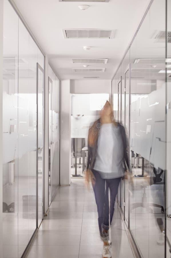 Una persona que camina en el vestíbulo moderno de la oficina de negocios, falta de definición de movimiento, persona irreconocibl fotos de archivo