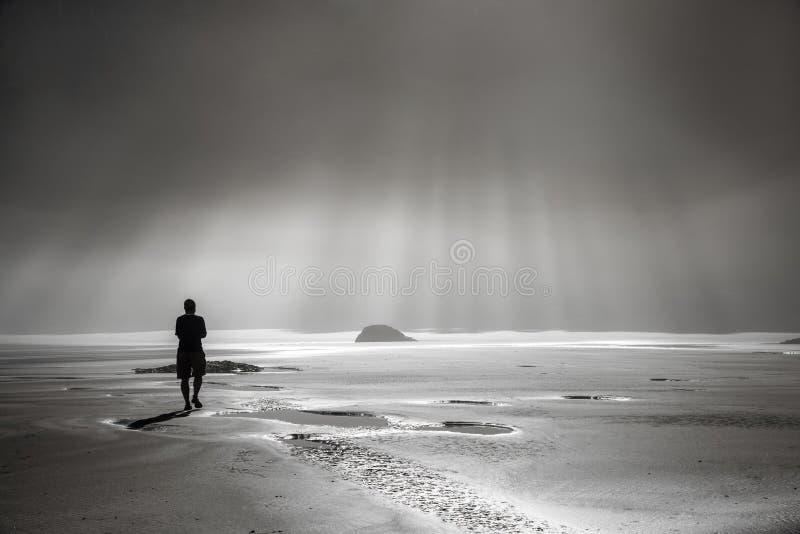 Persona que camina hacia rayos de sol foto de archivo libre de regalías