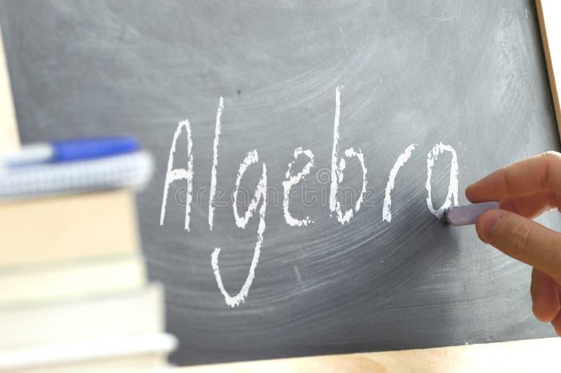 Una persona que escribe la álgebra de la palabra en una pizarra foto de archivo