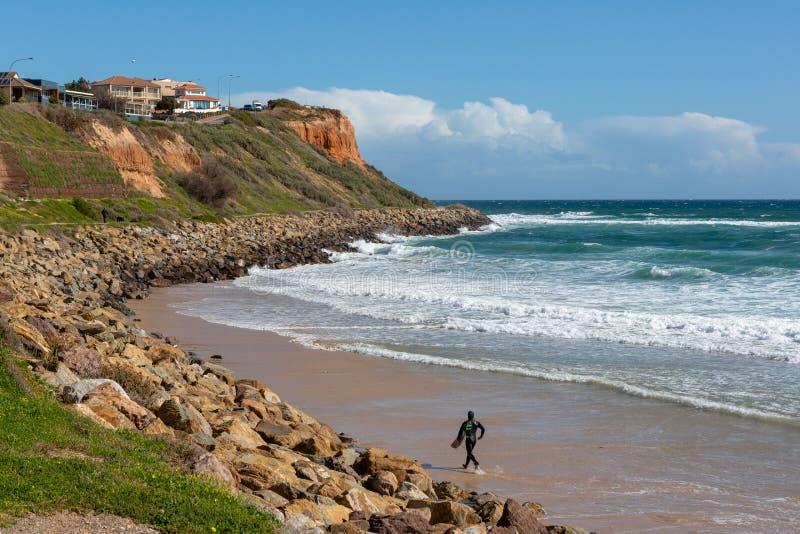 Una persona que practica surf que se rueda a lo largo de la arena al agua en Christies Bea imagen de archivo