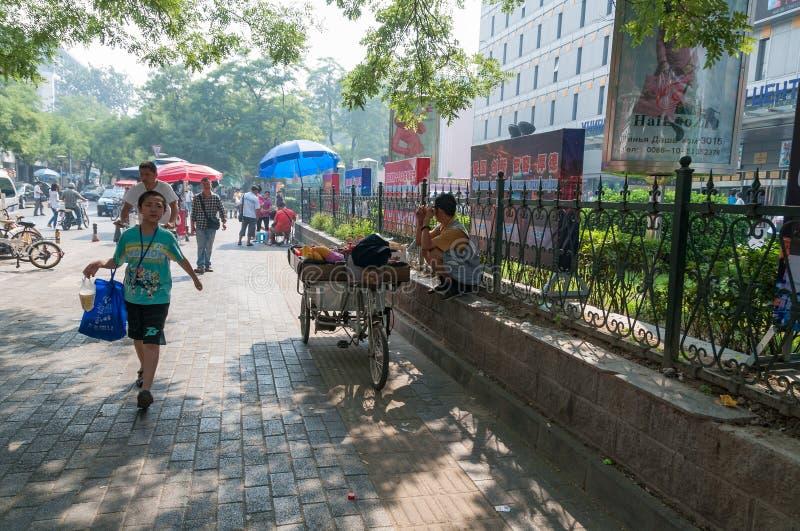 Una persona que vende las frutas de la bicicleta y a la gente del carrito que caminan la calle fotos de archivo libres de regalías