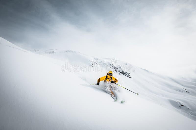 Una persona in rivestimento luminoso sta sciando in alte montagne Il Tirolo, Austria tempo soleggiato immagine stock libera da diritti