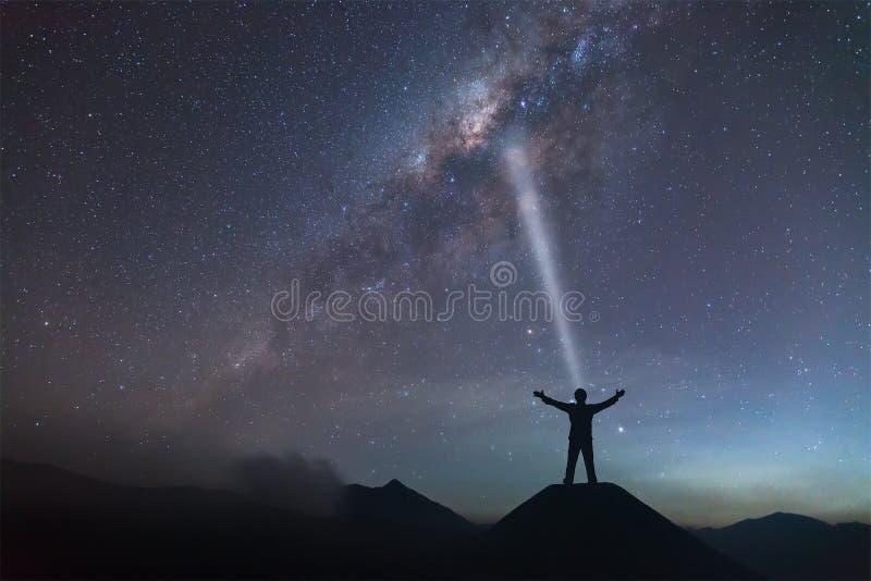 Una persona se está colocando al lado de la mano de la extensión de la galaxia de la vía láctea encendido imagen de archivo