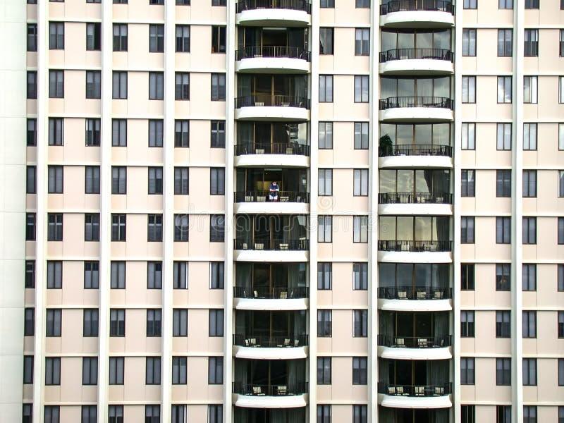 Una persona solitaria se coloca en el balcón de un hotel grande imágenes de archivo libres de regalías