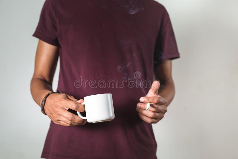 una persona sosteniendo una taza de café y un cigarrillo imagen de archivo libre de regalías