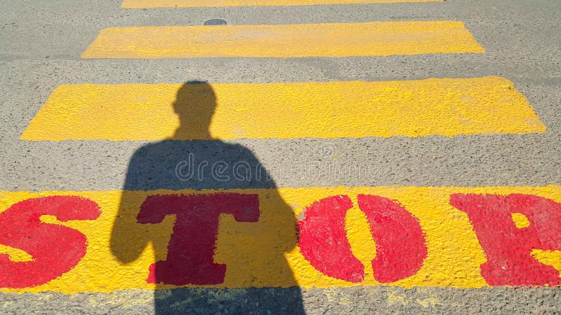 Una persona sta all'inizio di un passaggio pedonale, in cui è scritto la fermata e le attese per il tempo del passaggio, sul gial immagine stock