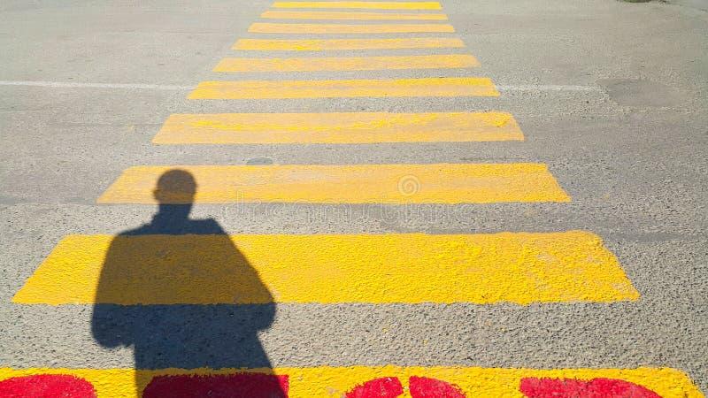 Una persona sta all'inizio di un passaggio pedonale, in cui è scritto la fermata e le attese per il tempo del passaggio, sul gial fotografie stock
