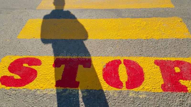 Una persona sta all'inizio di un passaggio pedonale, in cui è scritto la fermata e le attese per il tempo del passaggio, sul gial fotografia stock