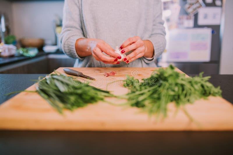 Una persona sta cucinando le verdure immagine stock