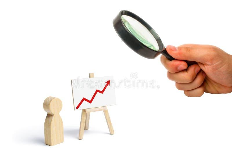 Una persona sta stando vicino ad un grafico con una freccia alta rossa finanziario fotografia stock libera da diritti