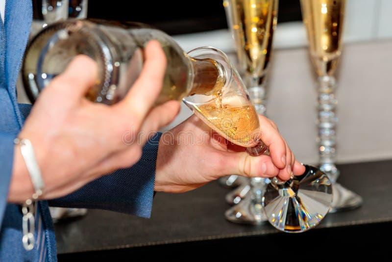 Una persona vertiendo champán en una copa de champán para hacer un brindis en la recepción foto de archivo