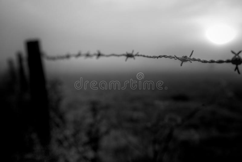Salida del sol sobre una cerca del alambre de púas imagenes de archivo
