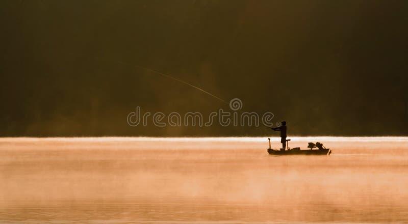 Una pesca del pescatore su un lago immagini stock libere da diritti