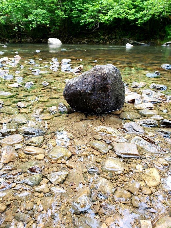 Una più grande roccia in un'insenatura rocciosa bassa con chiara acqua immagini stock libere da diritti