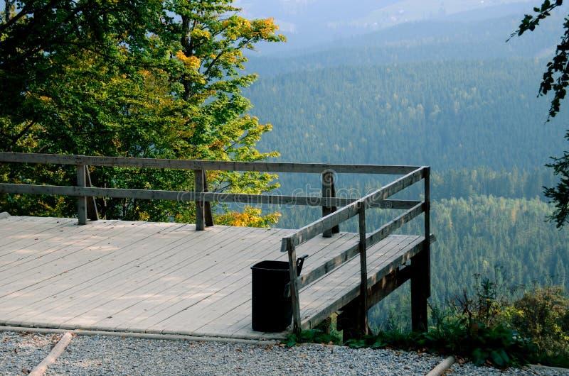 Una piattaforma di osservazione di legno sopra una scogliera che trascura i pendii di montagna coperti di foreste antiche immagini stock libere da diritti