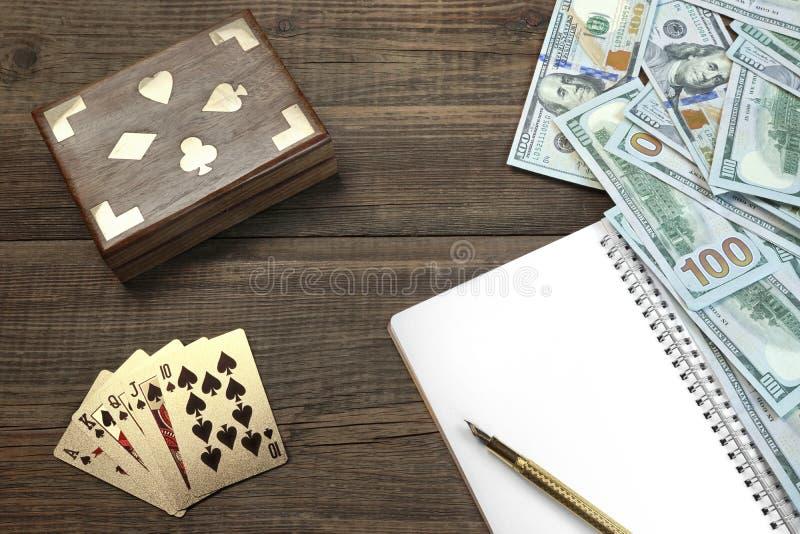 Una piattaforma, i soldi e un blocco note di due carte da gioco non aperta sulla Tabella immagini stock