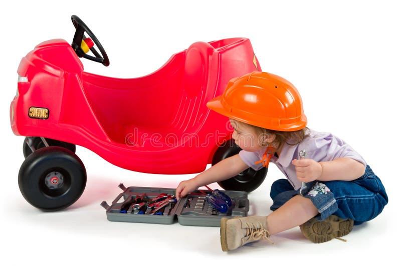 Una piccola bambina che gioca con l'automobile del giocattolo. immagini stock