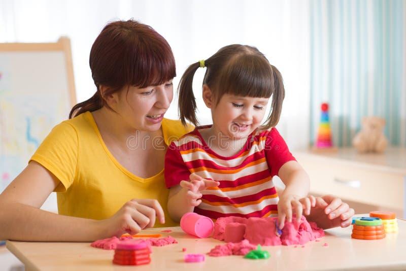Una piccola bambina sveglia e la sua mamma che giocano con la sabbia cinetica a casa immagini stock libere da diritti