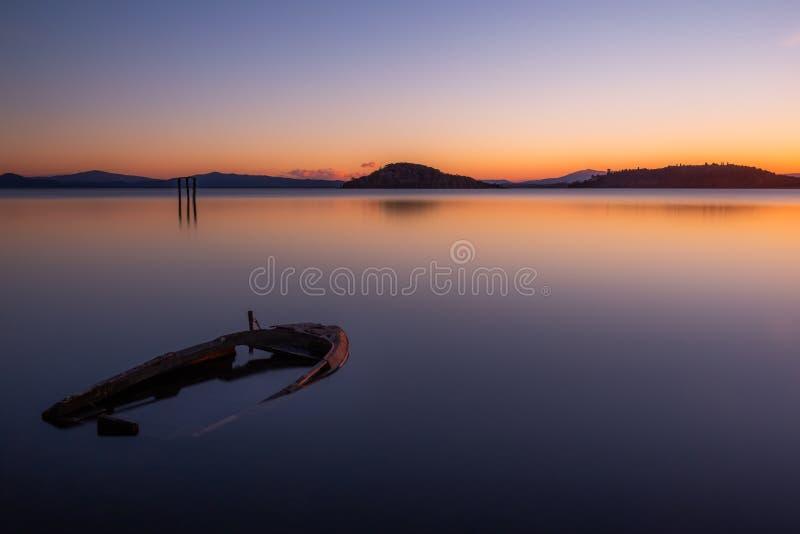 Una piccola barca al crepuscolo quasi completamente sinked nel lago Umbria, Italia Trasimeno immagine stock libera da diritti