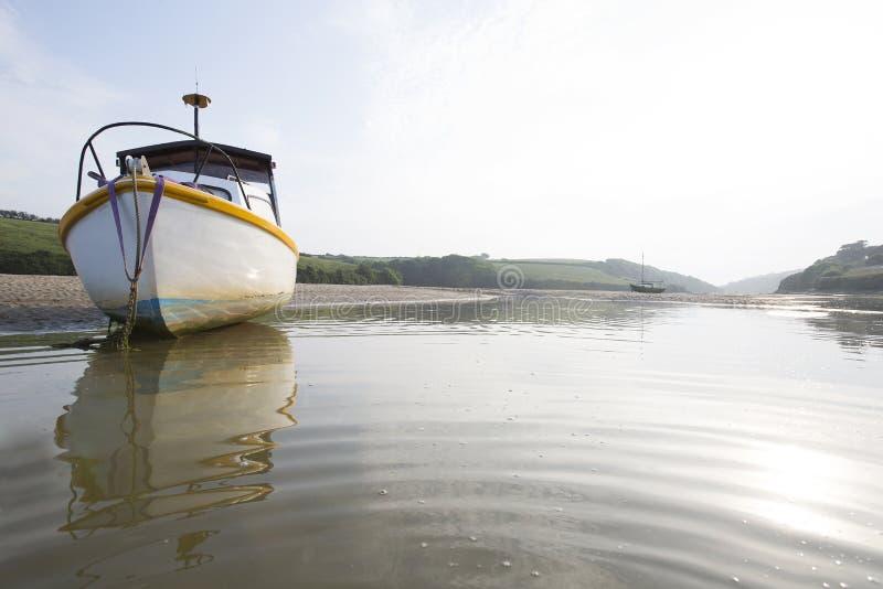 Una piccola barca a vela che si siede sulla banca della sabbia del fiume Gannel, in Cornovaglia fotografie stock libere da diritti