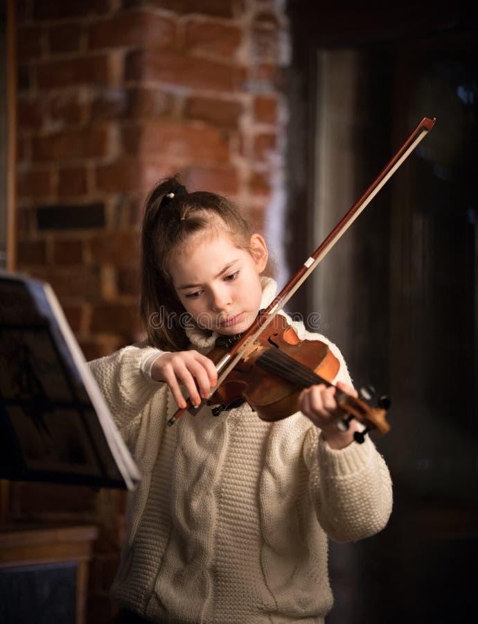 Una piccola bella ragazza in maglione bianco che gioca violino fotografia stock libera da diritti