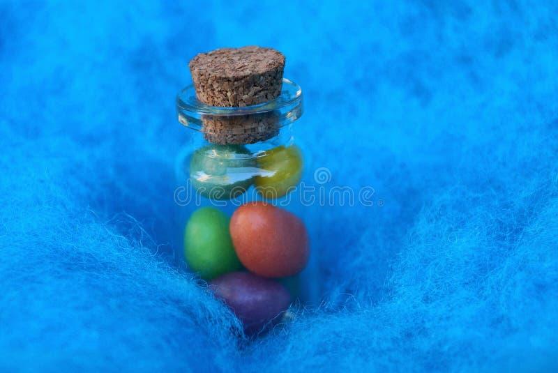 Una piccola bottiglia decorativa di vetro con i ciottoli colorati sta in un tessuto blu della lana immagini stock