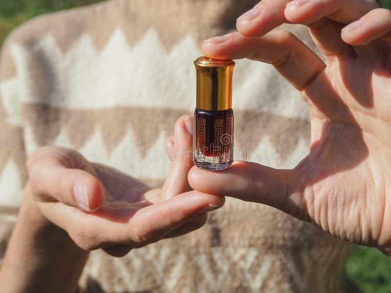 Una piccola bottiglia di vetro dell'olio del agarwood in palme femminili Olio profumato fotografia stock