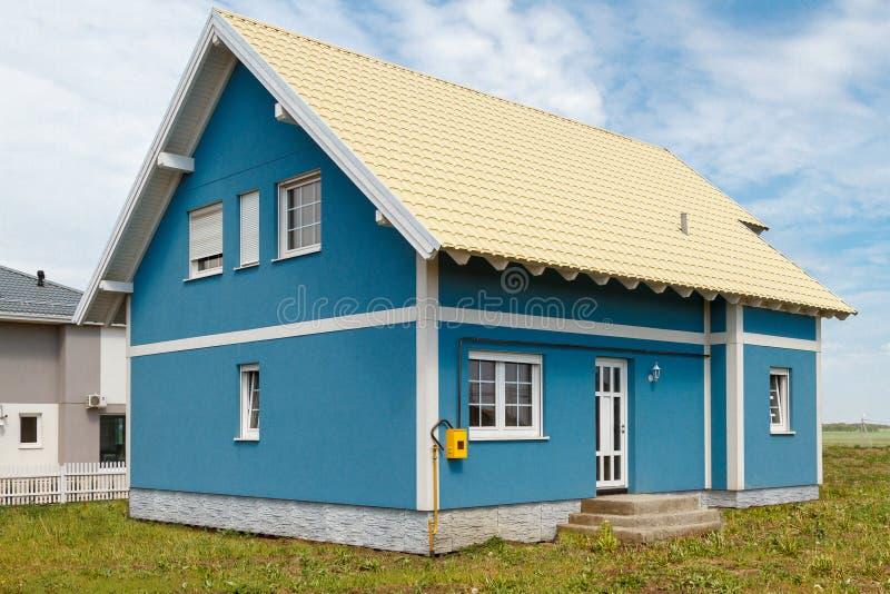 Una piccola casa blu con le finestre bianche e un tetto giallo-chiaro del metallo fotografia stock libera da diritti