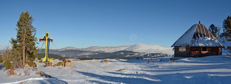 Una piccola casa di legno e una cabina di funivia nell'inverno, Gorny Altai, Siberia, Russia fotografia stock