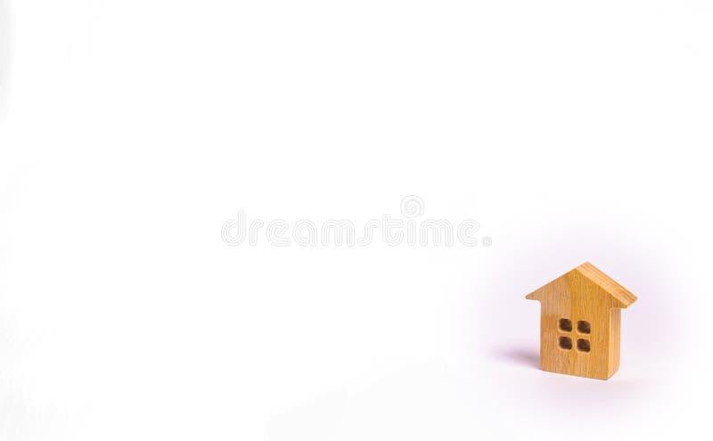 Una piccola casa di legno sta su un fondo bianco Il concetto di acquisto e di vendita del bene immobile, affittante Ricerca di un fotografie stock