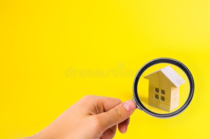 Una piccola casa di legno sta su un fondo giallo immagine stock