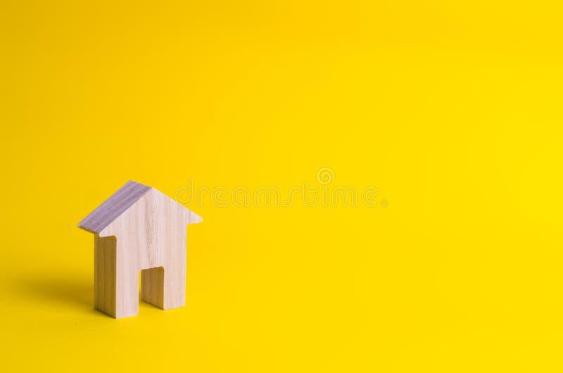 Una piccola casa di legno sta su un fondo giallo fotografia stock libera da diritti