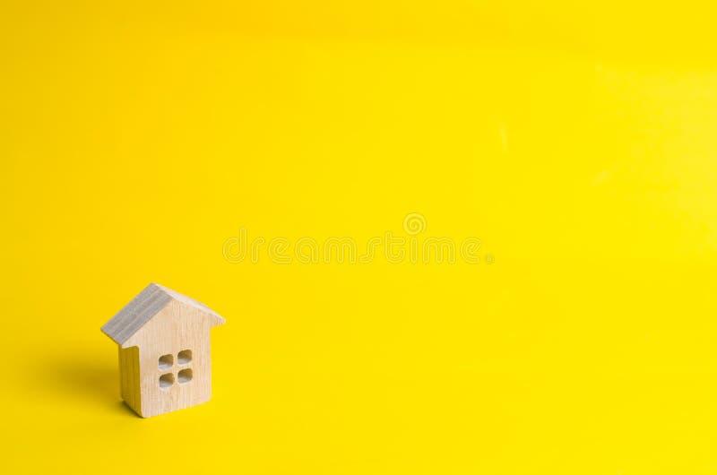 Una piccola casa di legno sta su un fondo giallo Il concetto di acquisto e di vendita del bene immobile, affittante Ricerca di un immagine stock libera da diritti