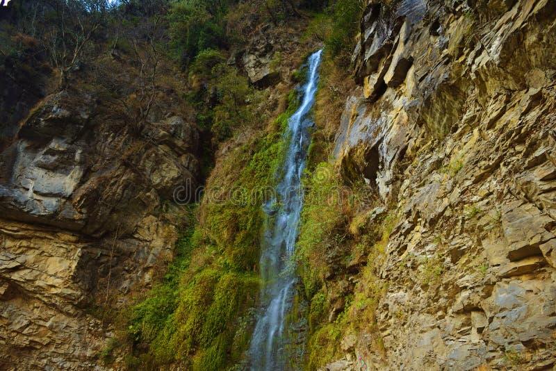 Una piccola cascata che gocciola giù un cliffside coperto in vegetazione fertile sulla strada a Hana nel Bhutan immagini stock libere da diritti